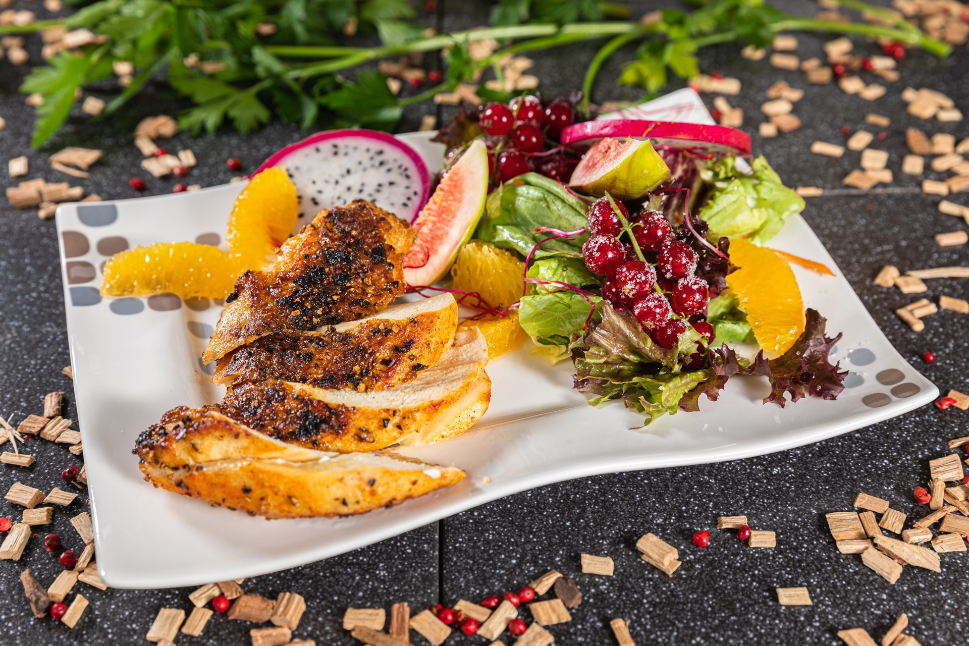 Mit Pfeffer-Himbeerrub eingestrichene Hähnchenbrust an frischem Blattsalat-Früchtereigen