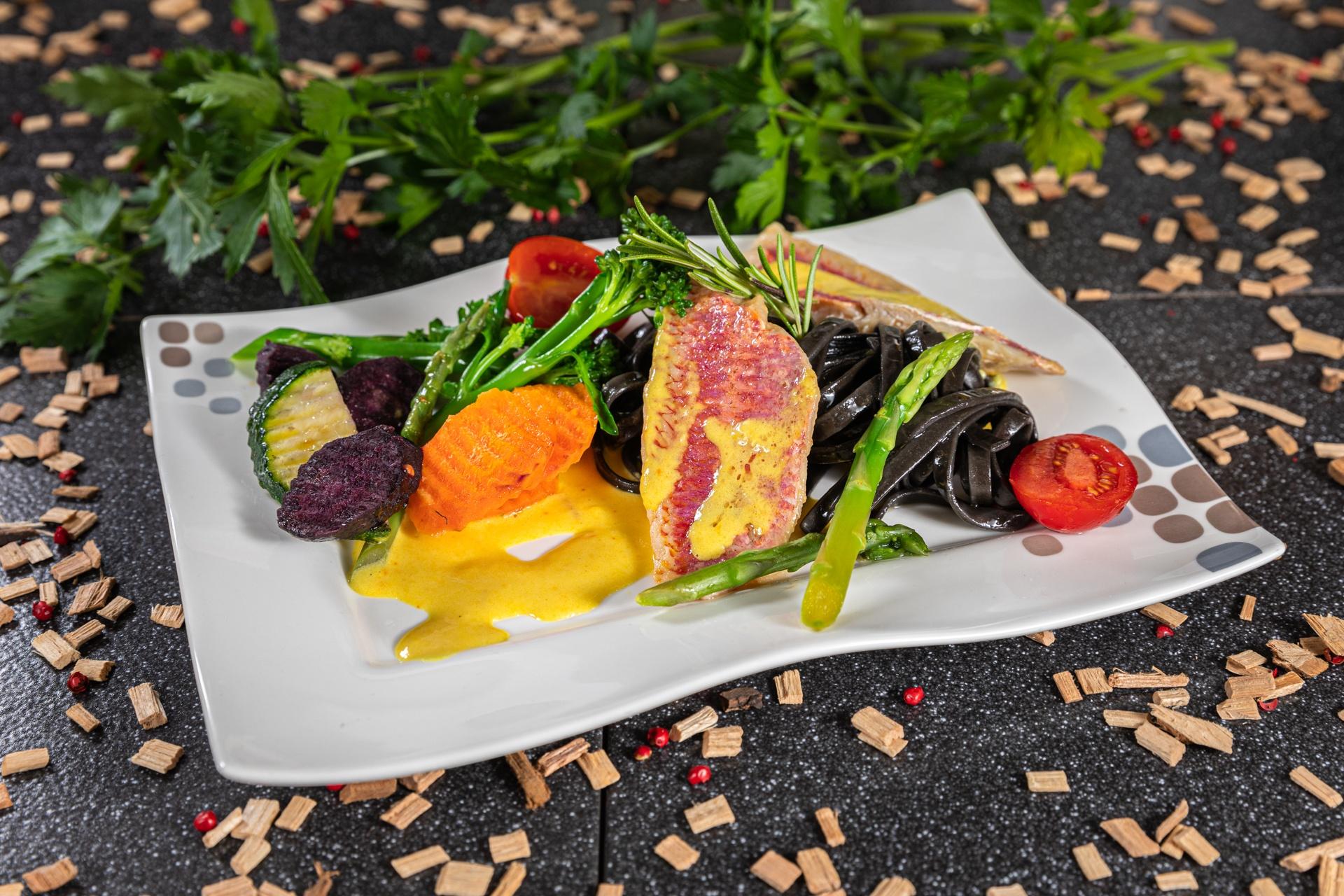 Felsenrotbarbe mit gelber Pimentosauce, schwarzen Spaghetti und buntem Gemüsereigen